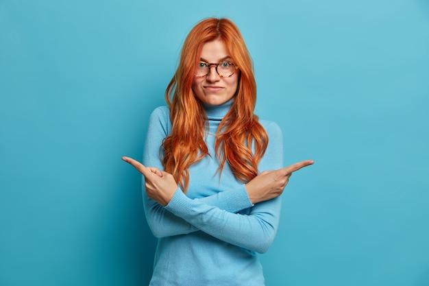 Mulher ruiva duvidosa escolhe entre duas maneiras: cruza os braços sobre o corpo indica em lados diferentes, vestida com roupas casuais.