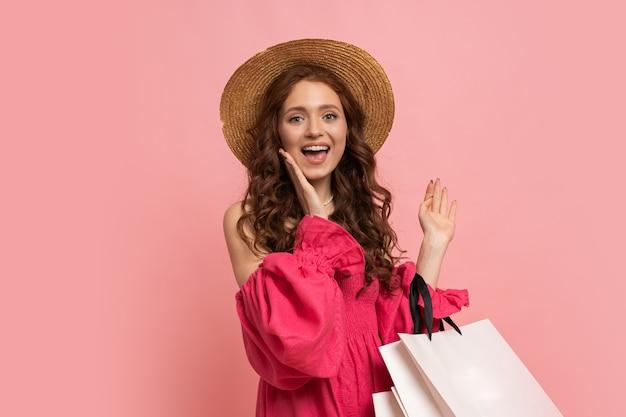 Mulher ruiva elegante com sacolas brancas, posando com um vestido rosa penhor com mangas sobre a parede rosa.