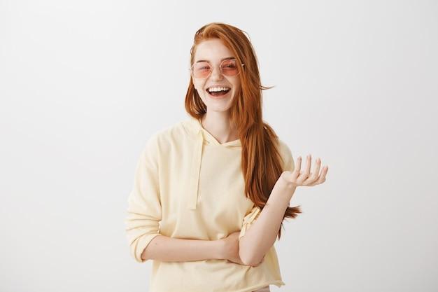 Mulher ruiva elegante de óculos escuros rindo e sorrindo feliz