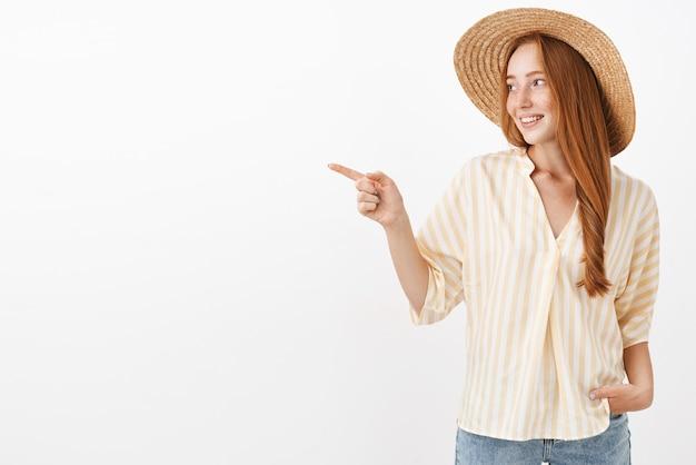 Mulher ruiva elegante, despreocupada e elegante, com chapéu de palha da moda e blusa amarela de verão, apontando e olhando para a esquerda e se divertindo, curtindo um passeio pela cidade estrangeira, posando sobre a parede cinza
