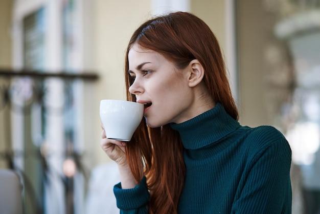 Mulher ruiva em um café de rua com uma xícara de café