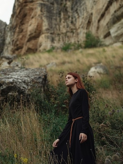 Mulher ruiva em um vestido preto, montanhas, viagens pela natureza