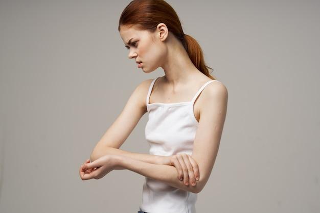 Mulher ruiva em uma camiseta branca em um bege gesticulando com as mãos dor no cotovelo