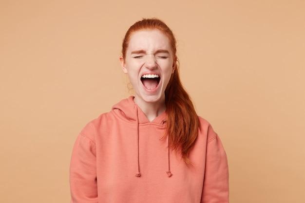 Mulher ruiva emocional, sentindo emoções violentas, abrindo amplamente a boca