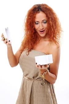 Mulher ruiva encantada com caixa de presente