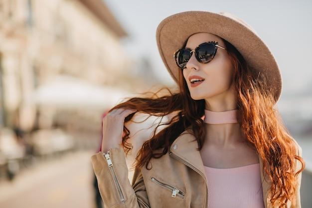 Mulher ruiva encantadora com óculos de sol elegantes e sonhadora olhando para longe