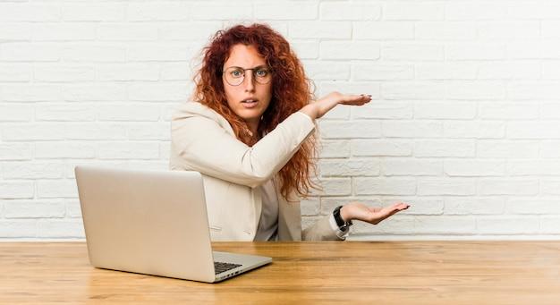 Mulher ruiva encaracolada jovem trabalhando com seu laptop chocado e espantado segurando um espaço de cópia entre as mãos.
