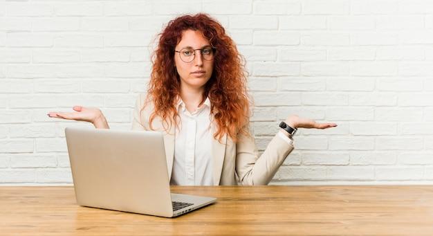 Mulher ruiva encaracolada jovem trabalhando com seu laptop faz escala com os braços, sente-se feliz e confiante.