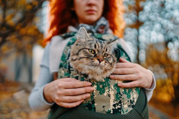 Mulher ruiva está andando pela rua carregando um gato em uma bolsa para a clínica veterinária