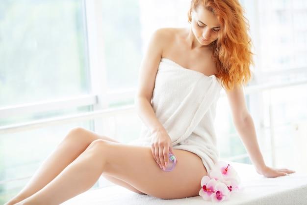 Mulher ruiva fazendo massagem gpl em casa em apartamento com janelas panorâmicas