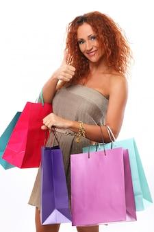 Mulher ruiva feliz com sacos de compras