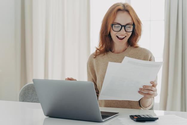 Mulher ruiva feliz e animada lendo carta de papel com notificação sobre o último pagamento da hipoteca