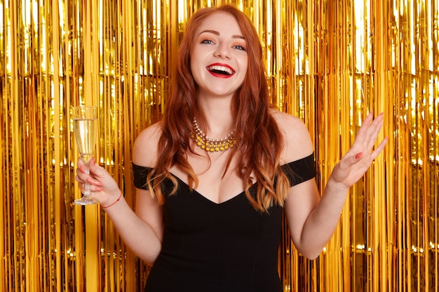 Mulher ruiva feliz e animada segurando um copo de vinho isolado na parede decorada com enfeites dourados, exclamando feliz, usando um vestido preto