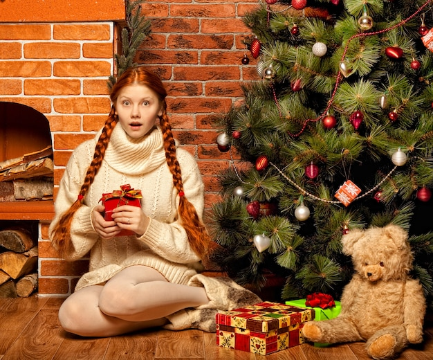 Mulher ruiva feliz segurando um presente de natal