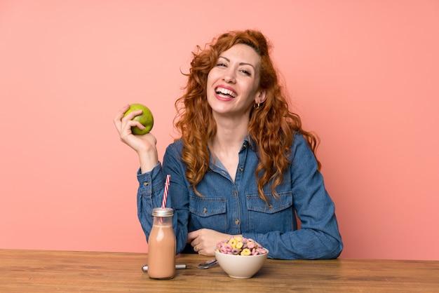 Mulher ruiva feliz tomando café da manhã
