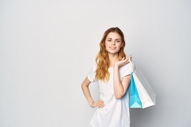 Mulher ruiva fofa com camiseta branca embalando estilo de vida de compras