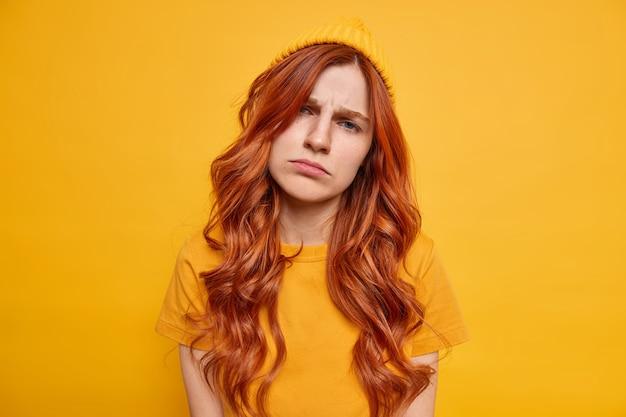 Mulher ruiva frustrada e triste inclina a cabeça com um ar infeliz, franze os lábios sente-se indiferente usa chapéu e camiseta casual posa contra a parede amarela vívida. conceito de emoções humanas negativas