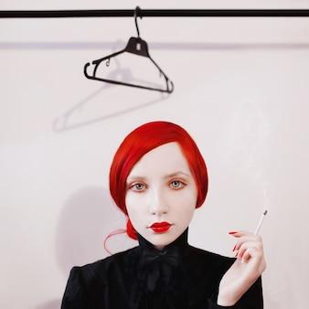 Mulher ruiva fuma um cigarro em uma garota de fundo branco em uma camisa preta e gravata borboleta com lábios vermelhos e unhas com a pele pálida, fumaça de cigarros