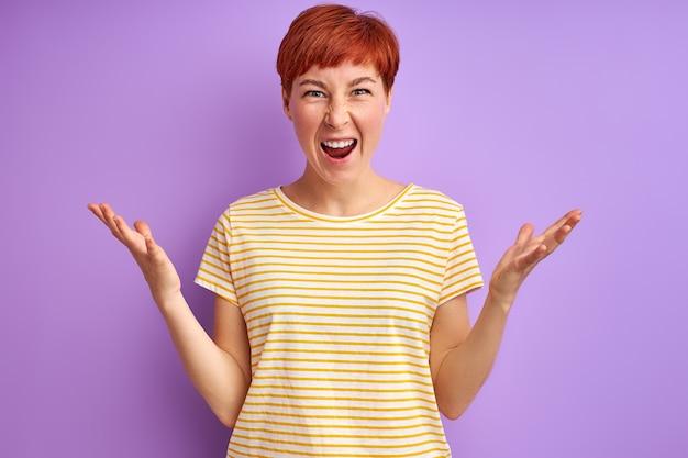 Mulher ruiva furiosa gritando isolada na parede roxa, discutindo