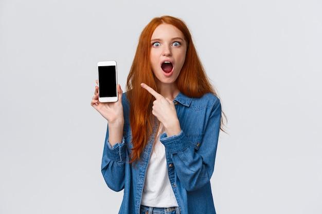 Mulher ruiva impressionada apontando para smartphone