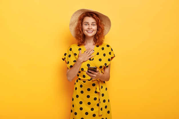 Mulher ruiva impressionada e satisfeita toca o peito, usa chapéu de verão e vestido de bolinhas amarelo