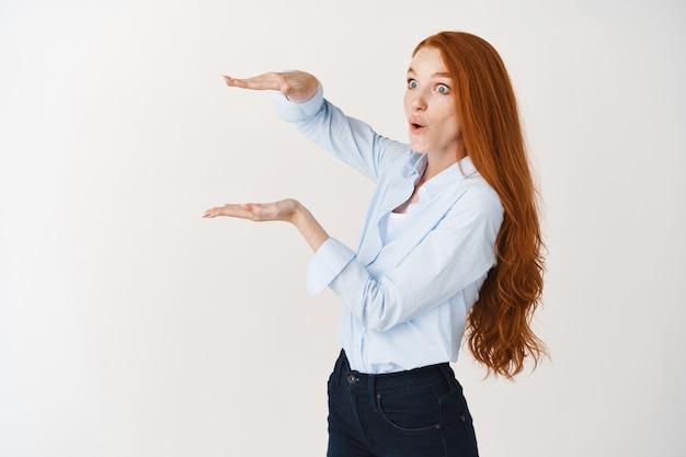 Mulher ruiva impressionada mostrando um objeto grande com as mãos, medindo algo grande e parecendo surpresa para a esquerda, parede branca