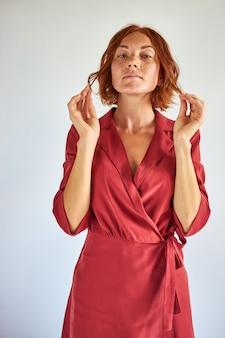 Mulher ruiva incomum de vestido vermelho posando olhando para a câmera, isolada no fundo branco