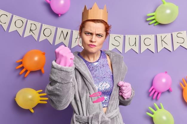 Mulher ruiva irritada em trajes casuais mostra punho cerrado afetado por coronavírus organiza festa sozinha fica em casa em poses de auto-isolamento balões coloridos internos guirlanda de papel na parede