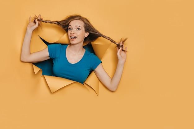 Mulher ruiva jovem alegre, vestida de camiseta turquesa