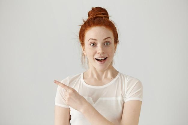 Mulher ruiva jovem animado com nó de cabelo, apontando o dedo indicador para os lados, levantando as sobrancelhas e mantendo a boca aberta, mostrando algo surpreendente