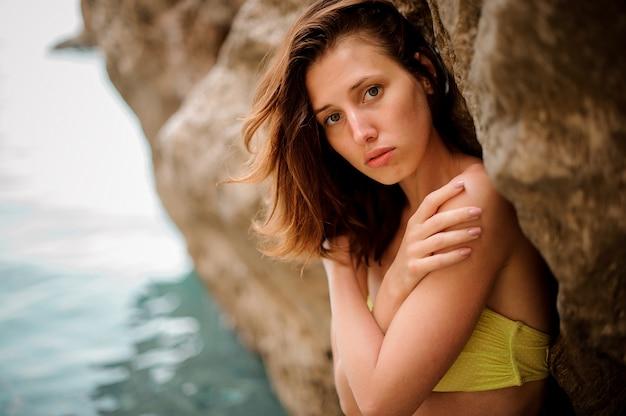 Mulher ruiva jovem atraente em amarelo perto da parede de pedra