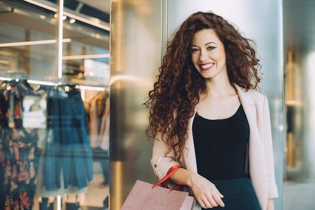 Mulher ruiva jovem bonita feliz fazendo compras