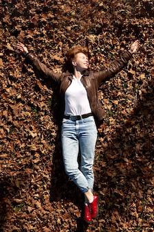 Mulher ruiva jovem feliz vestindo calça jeans, camisa branca e jaqueta de couro marrom no chão no parque outono e relaxante.