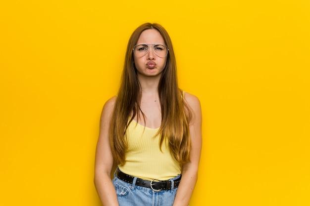 Mulher ruiva jovem ruiva com bochechas sardentas sopra, tem expressão cansada. conceito de expressão facial.