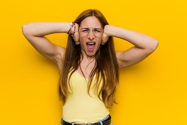 Mulher ruiva jovem ruiva com orelhas sardentas cobrindo com as mãos tentando não ouvir um som muito alto.