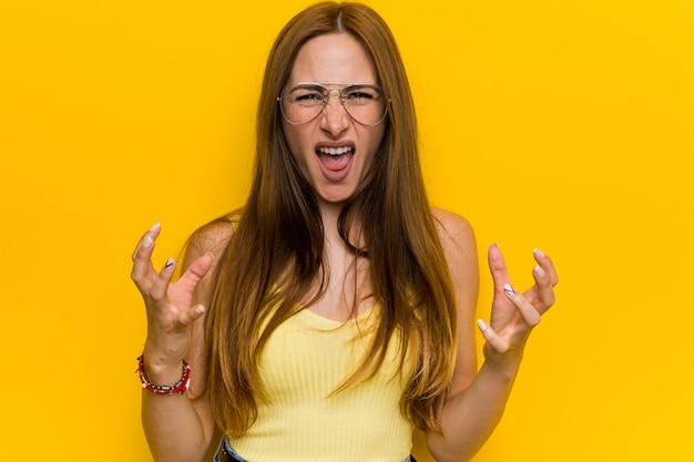Mulher ruiva jovem ruiva com virada sardenta gritando com as mãos tensas.