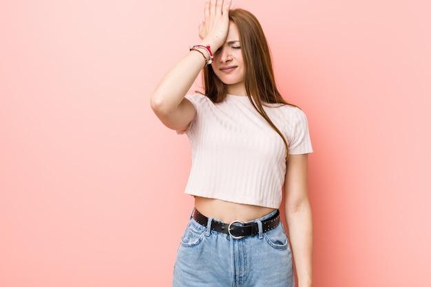 Mulher ruiva jovem ruiva contra uma parede rosa esquecendo algo, batendo na testa com a palma da mão e fechando os olhos.