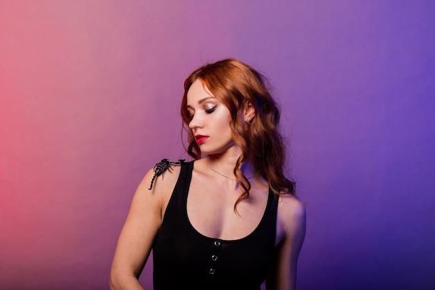 Mulher ruiva linda e sedutora maquiada com um escorpião em estúdio
