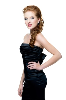 Mulher ruiva linda e sensual em um vestido preto, posando na parede branca