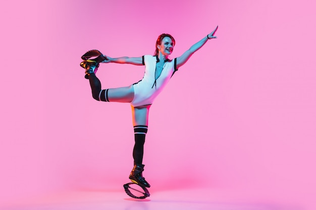 Mulher ruiva linda em um sportswear vermelho pulando em um kangoo salta sapatos na parede rosa