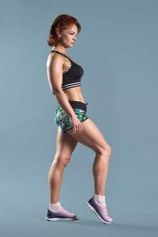 Mulher ruiva madura e atlética com camiseta e shorts esportivos fazendo exercícios de fitness