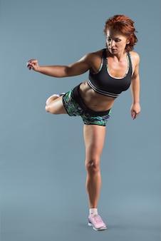 Mulher ruiva madura e atlética com camiseta esportiva e shorts fazendo exercícios de fitness, estúdio cinza