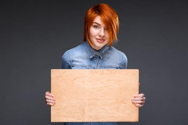 Mulher ruiva mostrando a placa de madeira