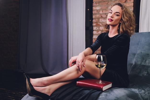 Mulher ruiva muito jovem, lendo um livro reclinado em um sofá de couro preto com um copo ou vinho tinto.