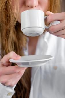 Mulher ruiva na camisa branca, bebendo café, close-up