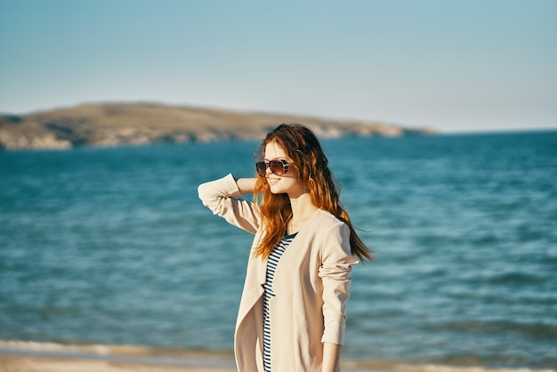 Mulher ruiva na praia usando óculos perto do modelo de camiseta de casaco bege de mar