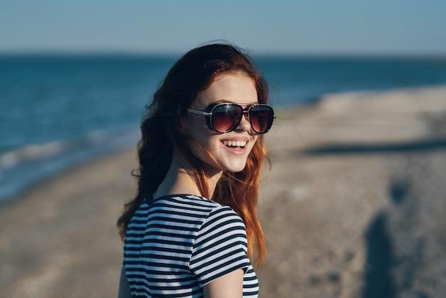 Mulher ruiva nas montanhas na natureza em óculos gesticula com as mãos na praia perto do