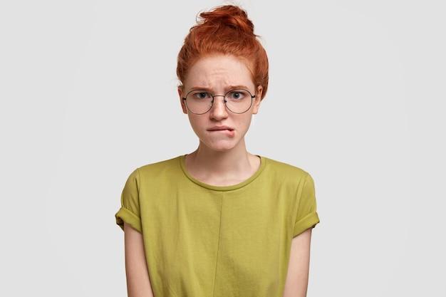 Mulher ruiva nervosa morde os lábios, tem expressão de descontentamento, tem dúvidas sobre algo, usa camiseta casual