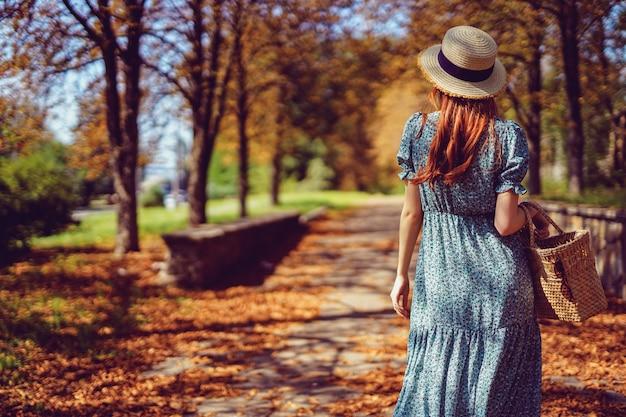 Mulher ruiva no verão indiano andando no parque procurando a estrada usa com um vestido esvoaçante