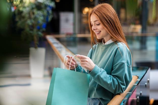 Mulher ruiva olhando para dentro da sacola de compras